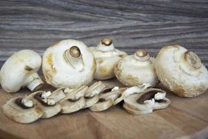 Champignonpaddestoelen liggen op een houten ondergrond foto
