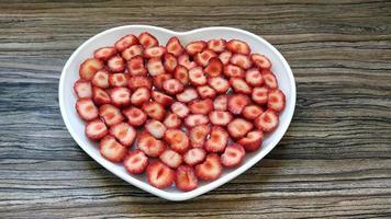 de gesneden aardbeien zitten in een hartvormig bord foto