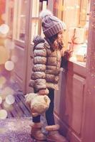 klein meisje voor het raam van een winkel, vol ingepakte cadeaus foto