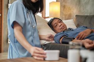 vrouwelijke arts die de gezondheid van Aziatische oudere mannelijke patiënt thuis controleert. foto