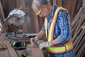 Aziatische senior timmerman man in houten fabriek. foto