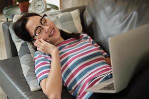 aziatische vrouw die thuis werkt, ligt en een mobiele telefoon gebruikt. foto