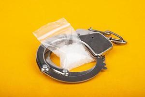 straf voor drugshandel, arrestatie van handboeien van drugsdealers en kristallen van mefedronamfetamine. foto