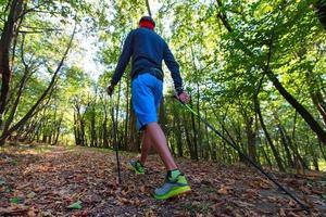 een man die nordic walking beoefent in het herfstbos tussen de bladeren foto