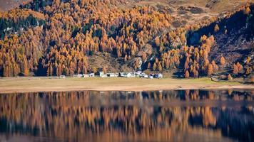 een spiegel van herfstplanten van een dorp aan een bergmeer foto