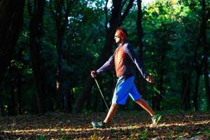 nordic walking in het herfstbos tussen de bladeren foto