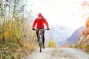 mountainbiker alleen op een onverharde weg foto