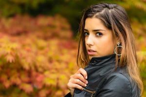 portret van mooi jong meisje met een achtergrond van herfstbladeren foto
