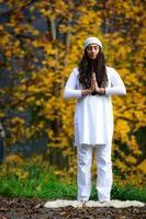 vrouw in het wit beoefent yoga in de natuur in de herfst foto