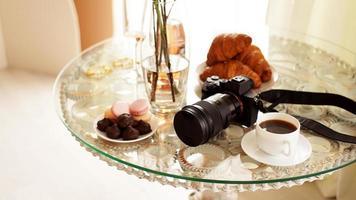 fotocamera met een lens op glazen tafel. kop koffie foto