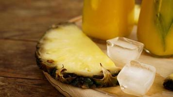 verse ananasschijfjes en ijsblokjes op een houten ondergrond foto