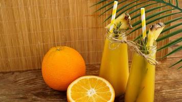twee flessen tropisch sap met papieren rietjes. sinaasappels en ananas foto