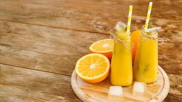 sinaasappelsap op een houten dienblad. gesneden sinaasappel en ijsblokjes foto