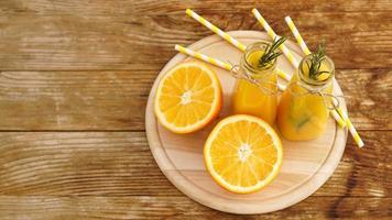 sinaasappelsap in glazen flessen. het sap is versierd foto