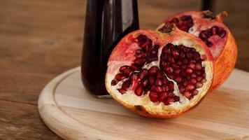 rijpe granaatappels met sap op houten achtergrond. foto