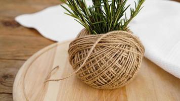 takjes rozemarijn en strengen jute touw op een houten foto