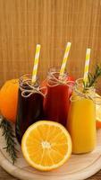 zelfgemaakte limonade in kleine flesjes. veelkleurige sappen en fruit foto