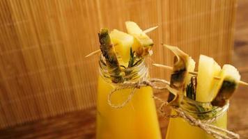 ananassap in een klein flesje. ananasschijfjes versieren de drank foto