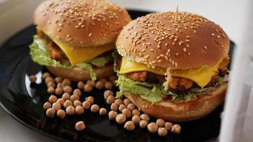 groenteburger met kikkererwtenkotelet. twee hamburgers op zwarte plaat foto