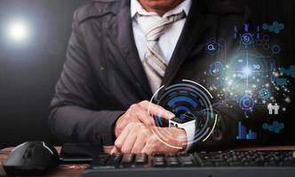 zakenman met behulp van smartwatch en zakelijke pictogram virtueel scherm foto