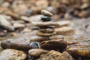 stenen piramide op kiezelstrand symboliseert stabiliteit, harmonie, balans foto