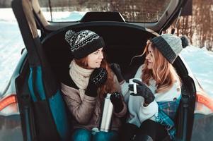 gelukkige vrienden in het winterbos. twee meisjes zitten in de kofferbak koffie te drinken foto