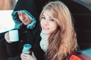 een man en een vrouw op de vrachtwagen van de auto. een gelukkig stel foto