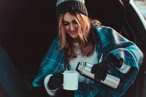 jonge vrouw zittend op auto kofferbak met koffiekopje foto