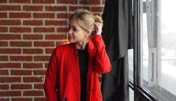 zakenvrouw blije glimlach draag rode jas over kantoorbakstenen muur foto