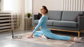 mooie jonge vrouw die thuis fitnessoefeningen doet met haar laptop foto