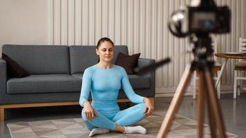 vrouwelijke blogger die thuis sportvideo opneemt. yoga houding foto