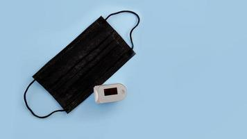 medisch zwart masker en oximeter op een blauwe achtergrond foto