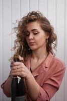 een jonge vrouw met krullend haar opent een fles champagne foto