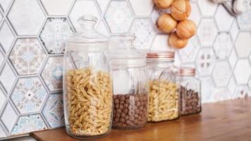 pasta in glazen potten. pasta op een houten aanrecht foto