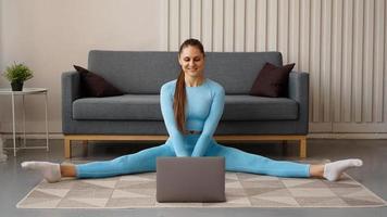 een mooie vrouw in een blauw trainingspak rekt zich uit foto