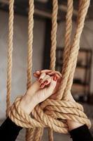 vastgebonden met een touw vrouwelijke handen met rode nagels foto