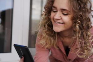 vrolijke prachtige jonge vrouw met krullend haar met smartphone foto