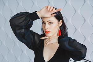 vrouw draagt een zwarte jurk, rode oorbellen in lichte studio foto