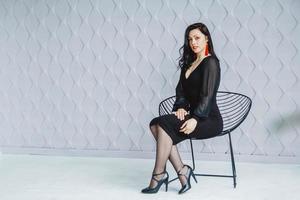vrouw die een zwarte jurk draagt en rode oorbellen draagt, zittend op een stoel foto