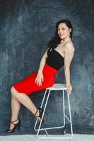 vrouw draagt een rode jurk zittend op een stoel op een grijze achtergrond foto