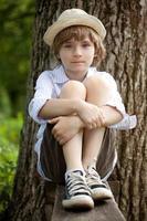 jongen in de hoed op de bank foto