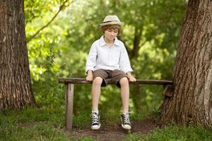 blonde jongen in een hoed, shirt, korte broek foto