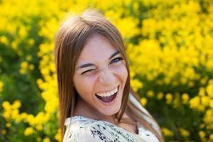 speelse jonge vrouw tussen gele bloemen foto