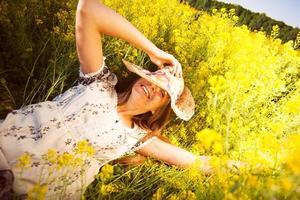 gelukkige vrouw die tussen gele wilde bloemen ligt foto