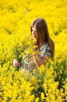 meisje op het gebied van gele bloemen foto