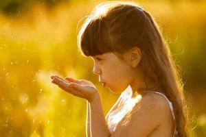 meisje blaast op zaden in de handpalmen foto