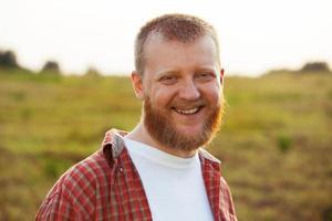 vrolijke, bebaarde man in een rood shirt foto