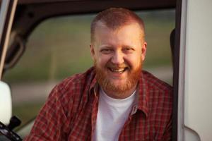 vrolijke man met rode baard in een geruit overhemd foto