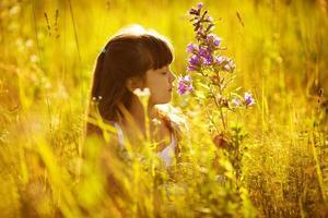gelukkig klein meisje dat aan een bloem ruikt foto