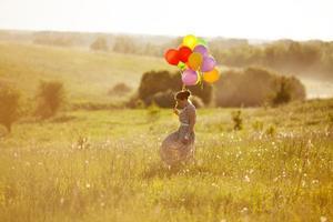 gelukkige jonge vrouw met ballonnen tussen een veld foto
